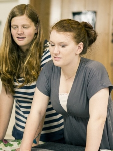 Tegan (right) now a counselor-in-training at YEA Camp works with camper Gabbi on on her activism project at camp